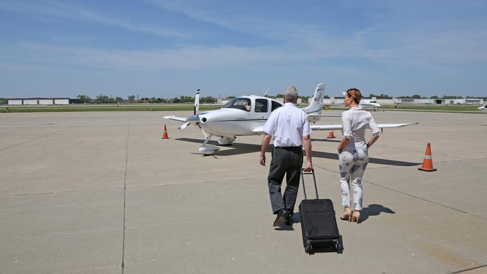 Passenger walking to airplane with pilot.
